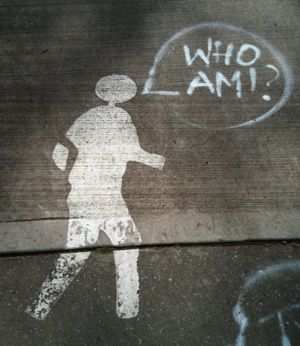 "Grafittied pedestrian with speech bubble ""Who am I?"""